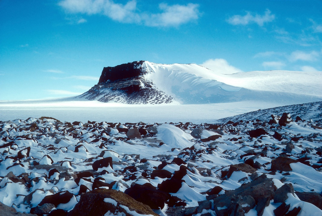 Antarctic mystery solved the archaeology news network sirius group exposures near mt fleming antarctica circa 1986 the pattern of snow behind rocks shows the prevailing winds across the east antarctic ice publicscrutiny Image collections