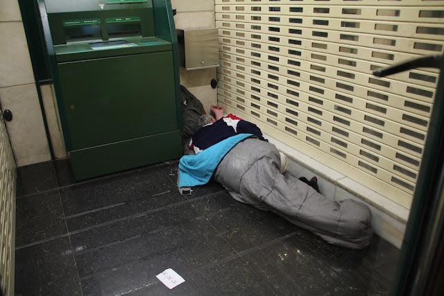 Una persona duerme en un cajero de la avenida de la Libertad