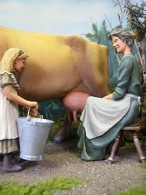 Model of a 19th-century woman milking a cow, with a child standing next to her with a bucket.