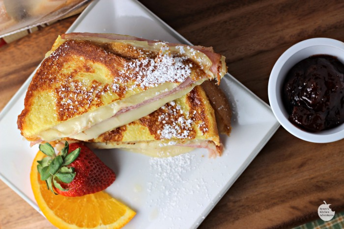 Monte Cristo Style Grilled Cheese Sandwich cut in half on plate