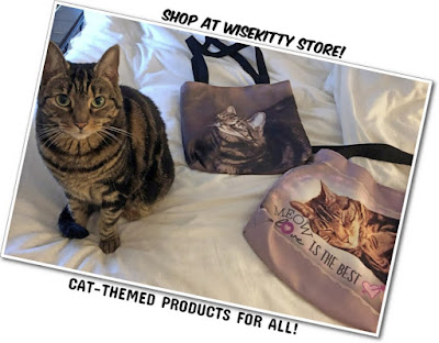 tabby cat sitting with tote bags