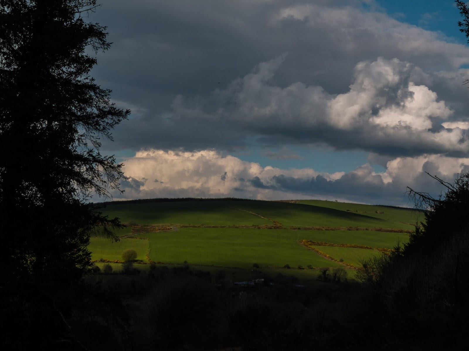 Clouds casting shadows on a hillside and mountain top in North Cork.