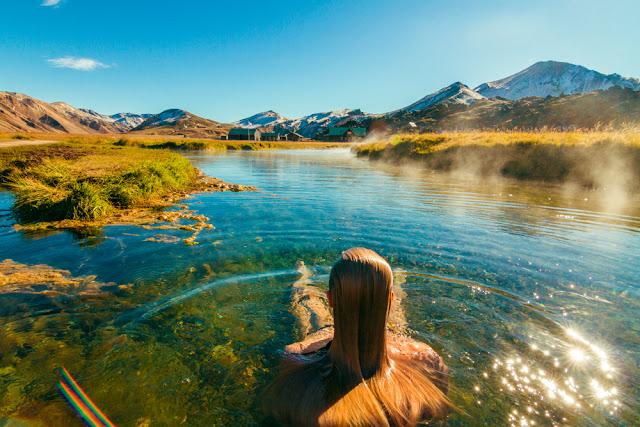 Female backpacker in Landmannalaugar hot spring in Iceland in August