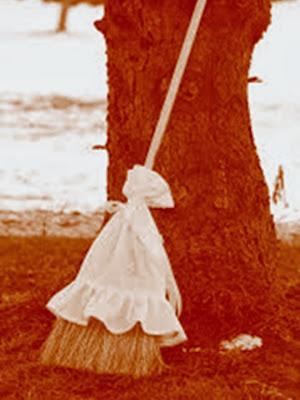 En la imagen un antigua escoba apoyada en un arbol