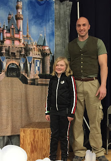 Young girl in black and red jogging outfit with a man in khaki pants and green shirt and green vest standing in front of a castle back drop