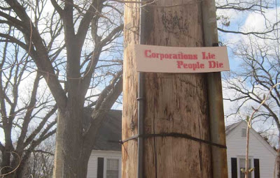 Handmade sign nailed to a utility pole, reading Corporations lie, people die