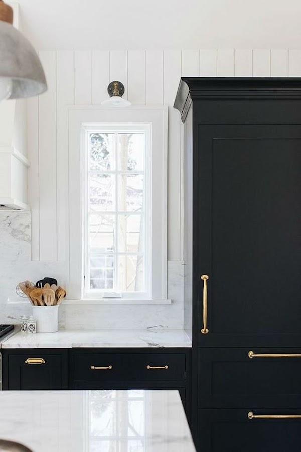 Cocina con muebles de madera negros y pomos (tiradores), en dorado