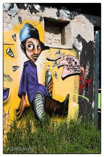 sapkás alak festékszóróval graffiti Szegeden a körtöltésen
