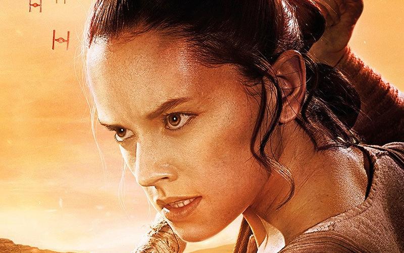 Na imagem: Recorte de um pôster mostrando o rosto da Rey de perto, a imagem é toda em tons de amarelo lembrando ao deserto, os olhos dela caramelo estão vivos, ela parece suada de esforço. Rey olha para frente com uma expressão determinada como quem está prestes a enfrentar alguém