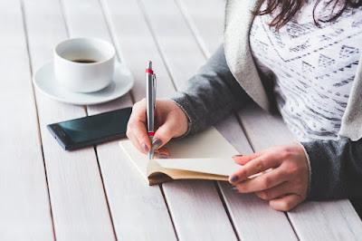 Chica escribiendo con móvil y taza de café.