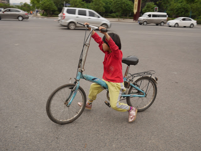 small girl walking a bike while siting on the crossbar