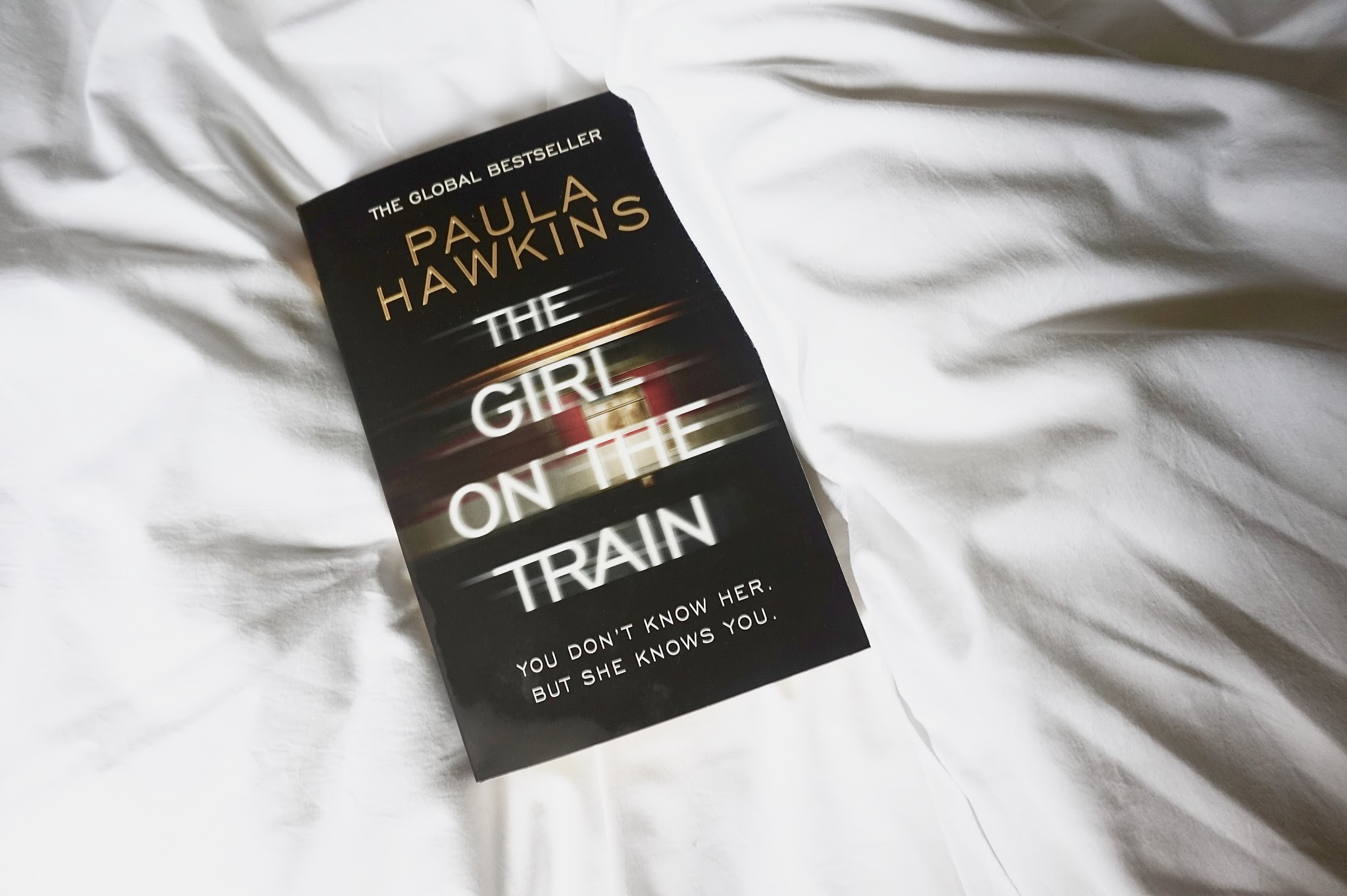 The Girl on the Train book on white bed