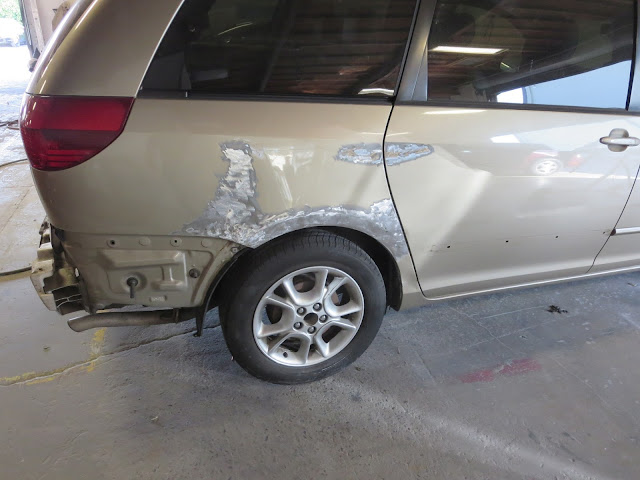 Big dents in side of Toyota Sienna during collision repair.