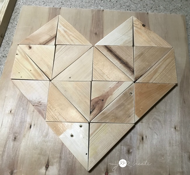 measuring wooden triangle heart on scrap plywood