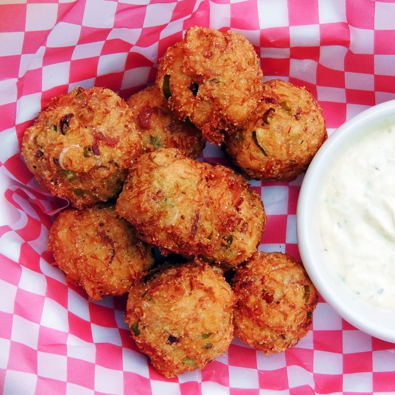 Hush Puppies made with crab on a red and white checkered paper