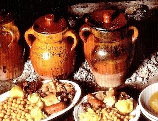 Platos de cocido junto a los pucheros de barro en los que se ha cocinado a fuego lento en las ascuas de la lumbre. Ésta se considera la manera de btener el mejor cocido.