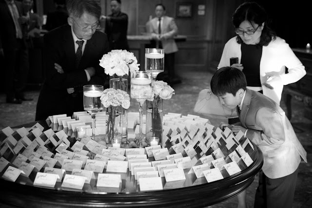 Guests search table cards to find their seats at Bridgeview Yacht Club for Jin and Christopher's wedding reception