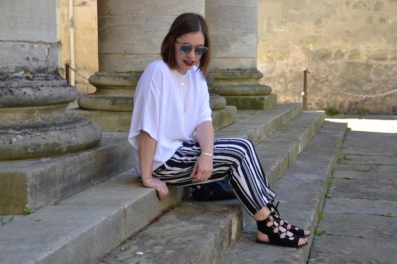 Blouse blanche H&M, pantalon fluide rayé Zara, sac Balenciaga, sandales noires Boohoo, lunette So Real, collier l'atelier d'Amaya