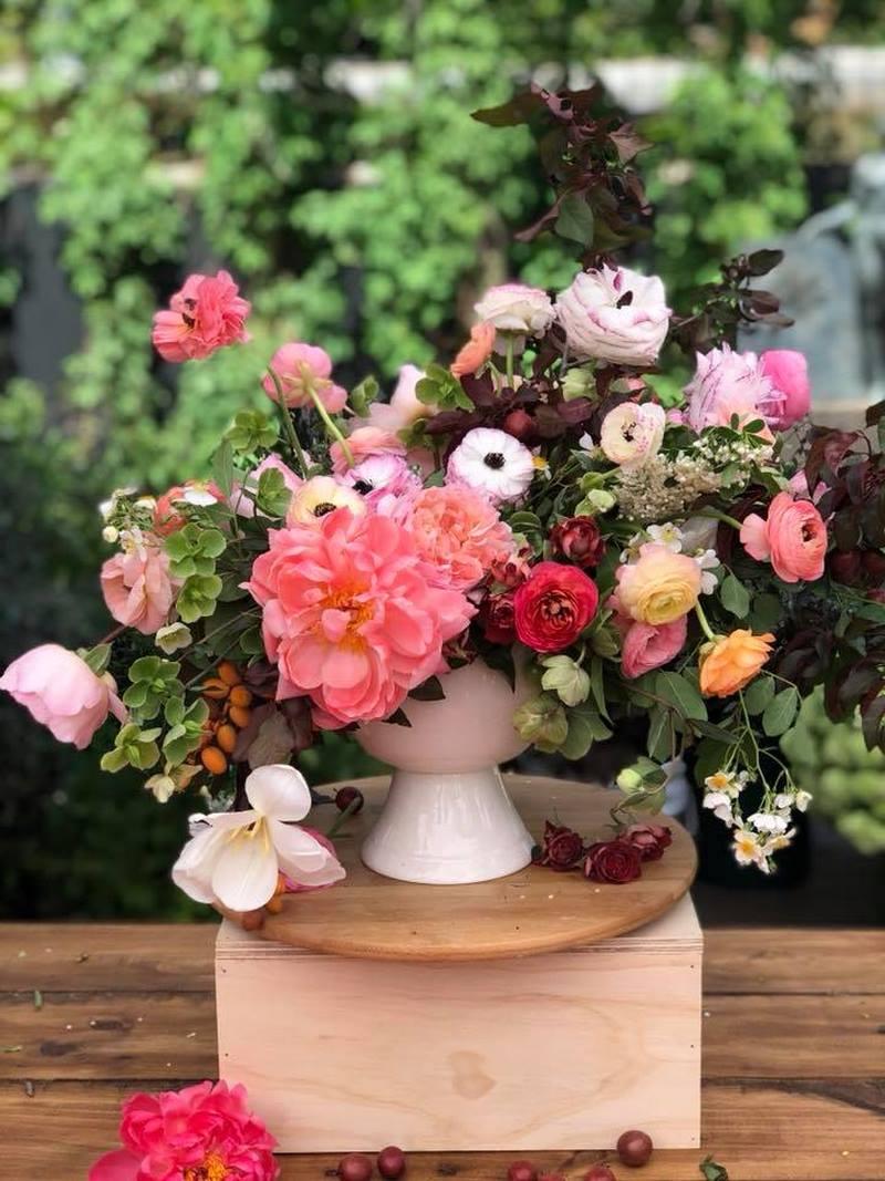 jarrón blanco, flores y frutos