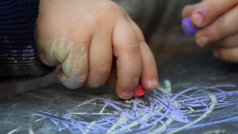 Mani di bimbo che disegnano con gessetti colorati