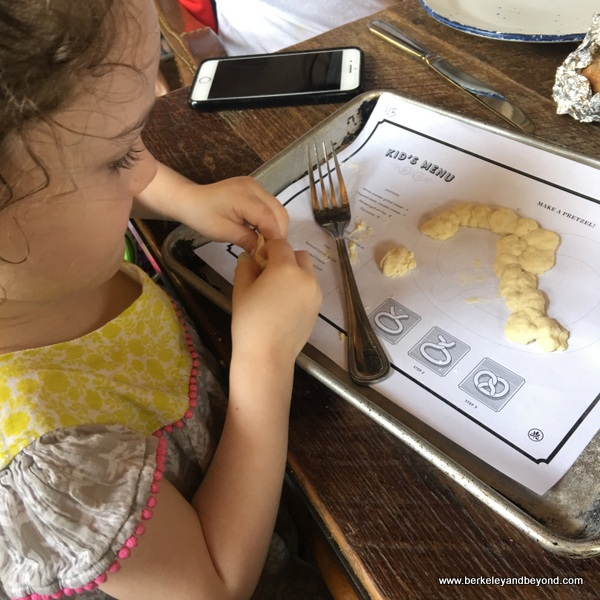 little girl plays with pretzel dough at Southerleigh Fine Food and Brewery in San Antoniio, Texas