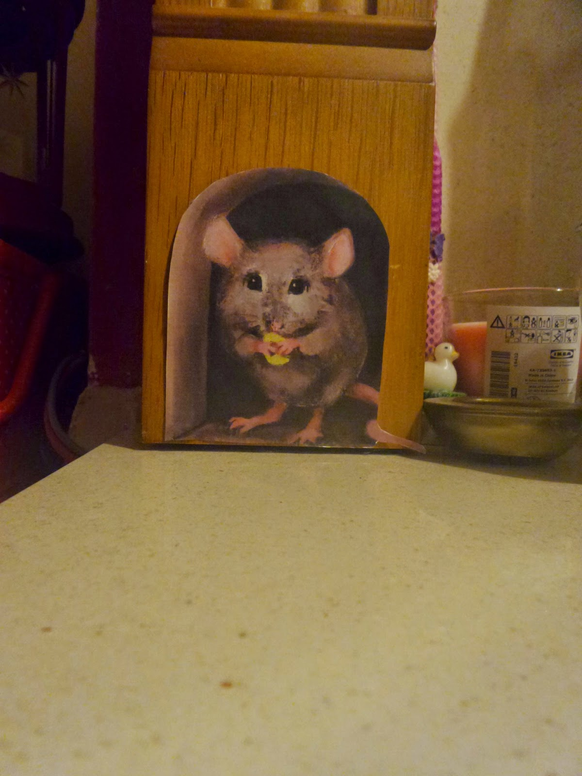 A paper mouse hole on the fireplace