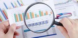 Mão segurando lupa para pesquisa de mercado