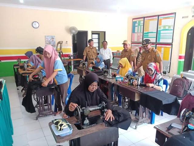 Ketua Apdesi Asahan Sujud Prayetno melihat ibu-ibu latihan menjahit.