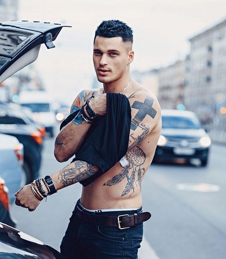 vemos a un hombre atlético lleva tatuaje de cruz grande en el hombro