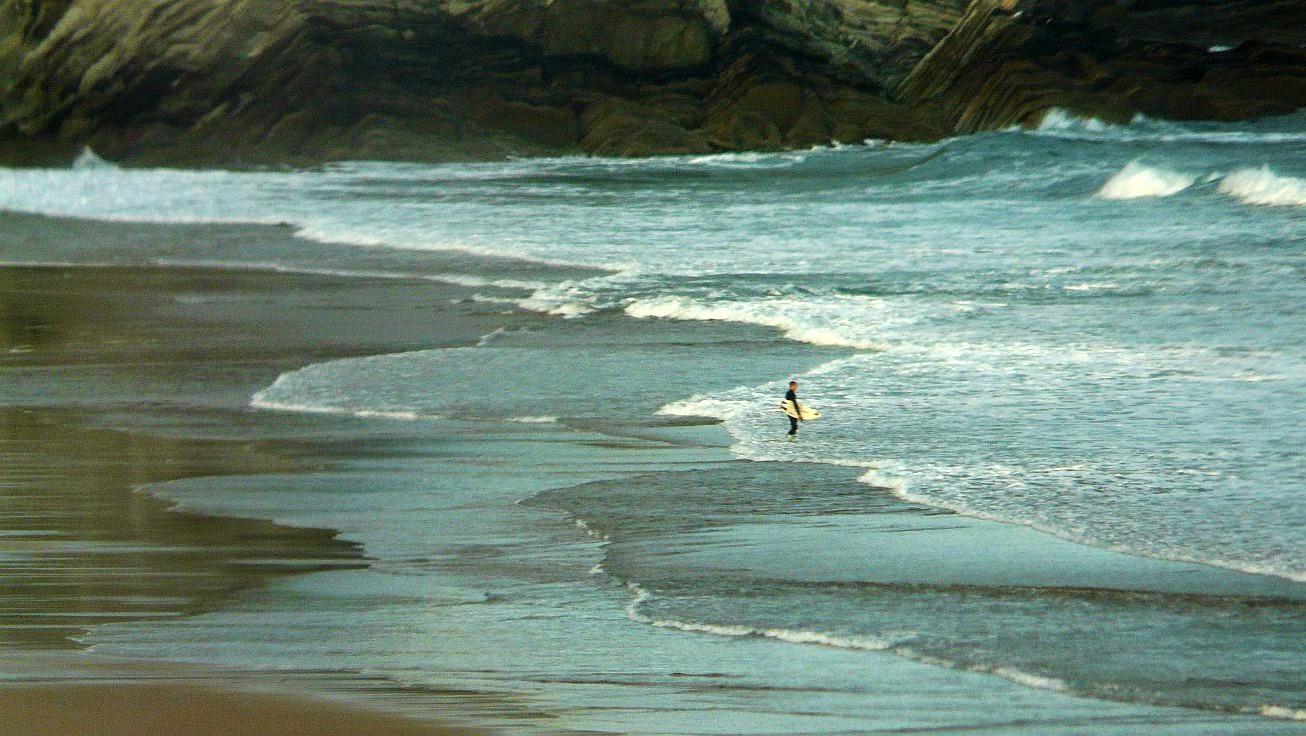 surfista entrando al agua sopelana