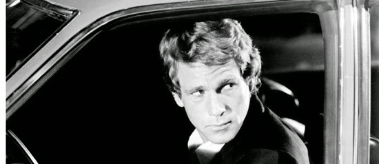 Black and White Still of Ryan O'Neal sat in a stationary car looking out the window