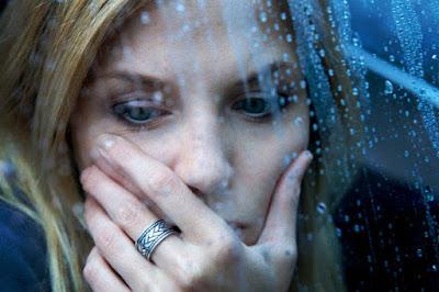 mujer tras un vidrio con aspecto triste