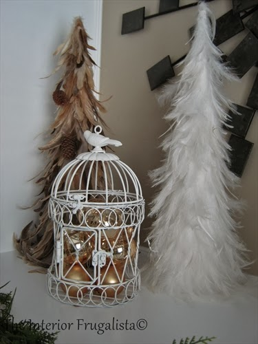 Bird cage filled with Christmas balls for the holidays.