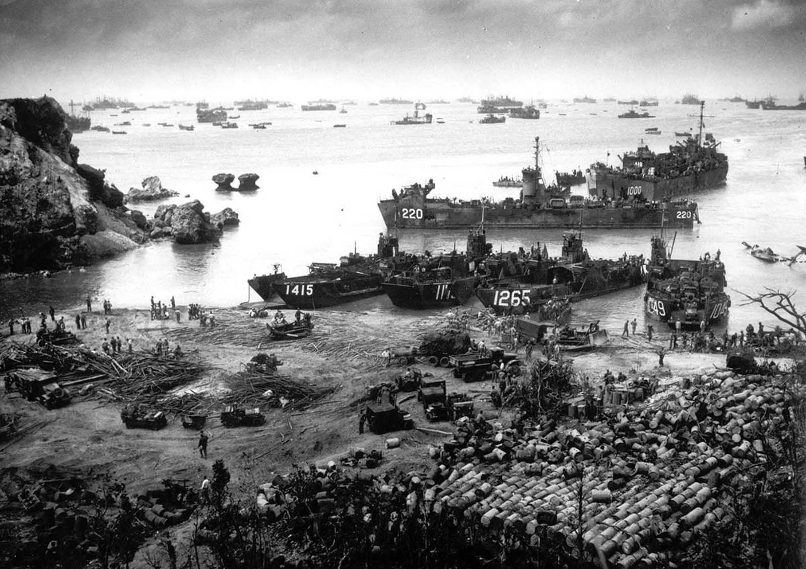 U.S. invasion forces establish a beachhead on Okinawa island, about 350 miles from the Japanese mainland, on April 13. 1945. Pouring out war supplies and military equipment, the landing crafts fill the sea to the horizon, in the distance, battleships of the U.S. fleet.