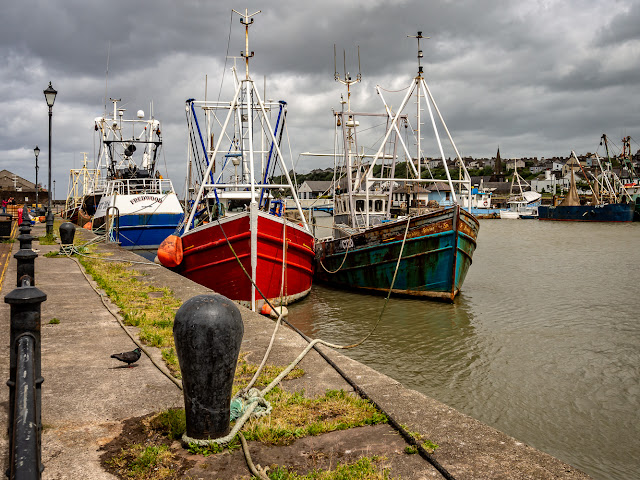 Photo of colourful fishing boats almost level with the top of the dock