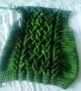 A peice of knitting laying flat, still live on a circular needle.  The are decreases visible to shape the underarms. There's a large central cable motif and two smaller cables on either side.  The knitting is done in a tonal yarn that varies between emerald green and almost black.