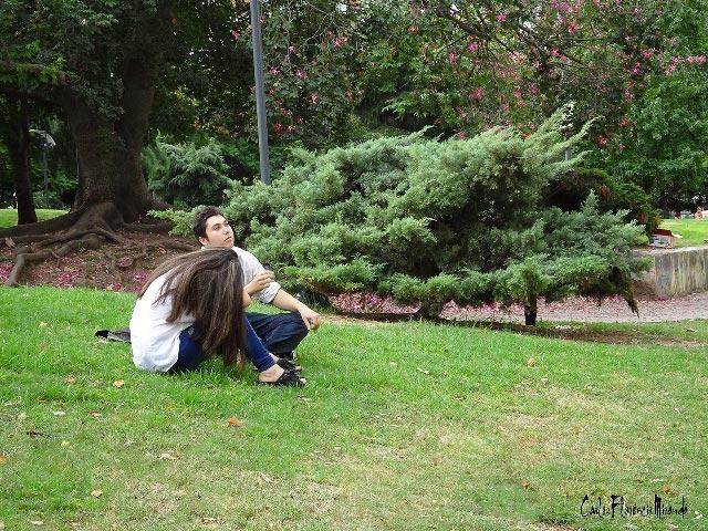 Pareja de jóvenes sentados en el césped del parque.
