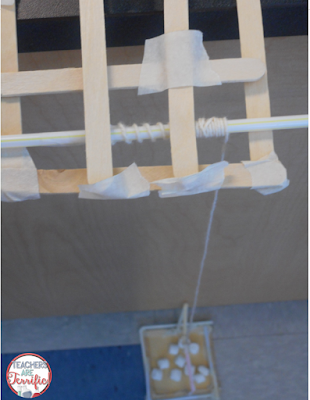 STEM Challenge: It's a rescue challenge! They have woven a straw through the craft stick platform at the top and by turning the straw they can wind up the platform on the ground.