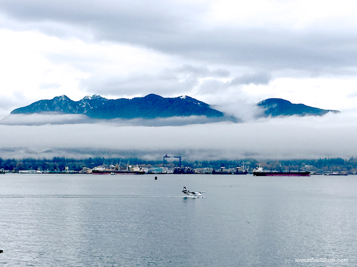 misty vancouver harbourfront with seaplane landing