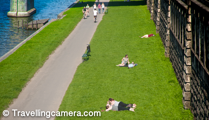 Here is a view of people soaking sun, walking around and indulged in other activities like cycling. This photograph is clicked from the bridge and these green patches are all around the banks of Vistula River.