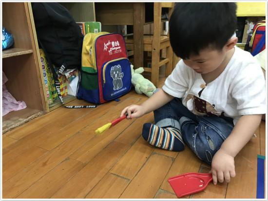 幼兒園孩子用可愛的小掃把道具,幫忙清潔地板。
