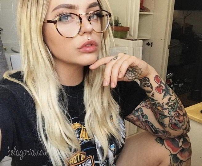 Modelo sentada en su cocina, lleva tatuajes de rosas
