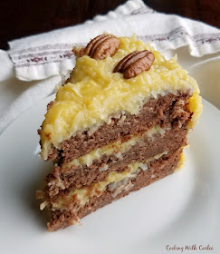 slice of german chocolate cake with golden coconut frosting and pecan halves