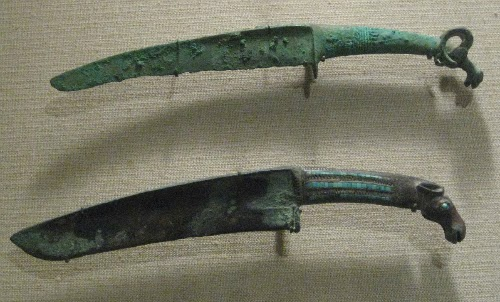 2 punhais (ou adagas) de bronze da dinastia shang, feitos há mais de 3 mil anos, com detalhes de cabeças de animais nos punhos, direto de frases de Sun Tzu e d'A Arte da Guerra.