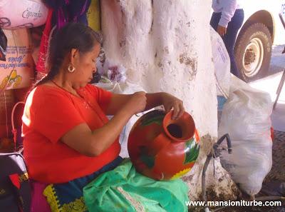 Artesana Michocana pintando su alfarería