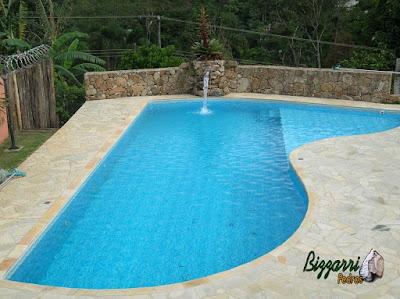 Construção de muro de pedra com pedra bruta com a construção da piscina de vinil, o piso do passeio da piscina com pedra caquinho de São Tomé em residência em Mairiporã-SP.
