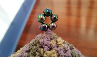 Close up of a pointed hat's ring of metallic-coloured beads which reflect and complement the colours of the hat.