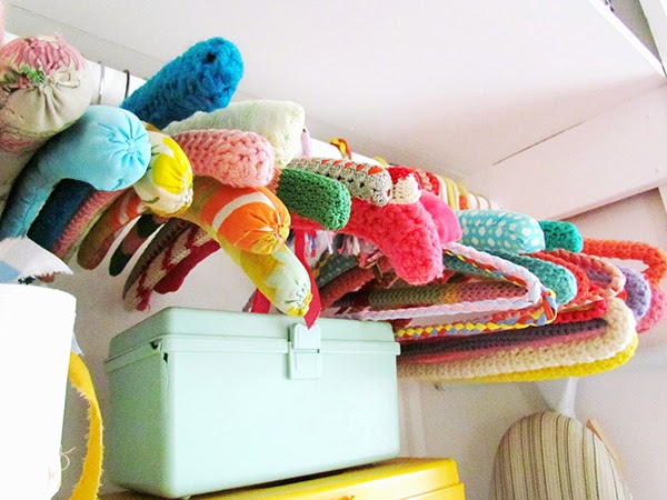 Crochet hangers and vintage sewing boxes being used for storage
