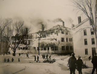 A black and white photograph of a burning hall.