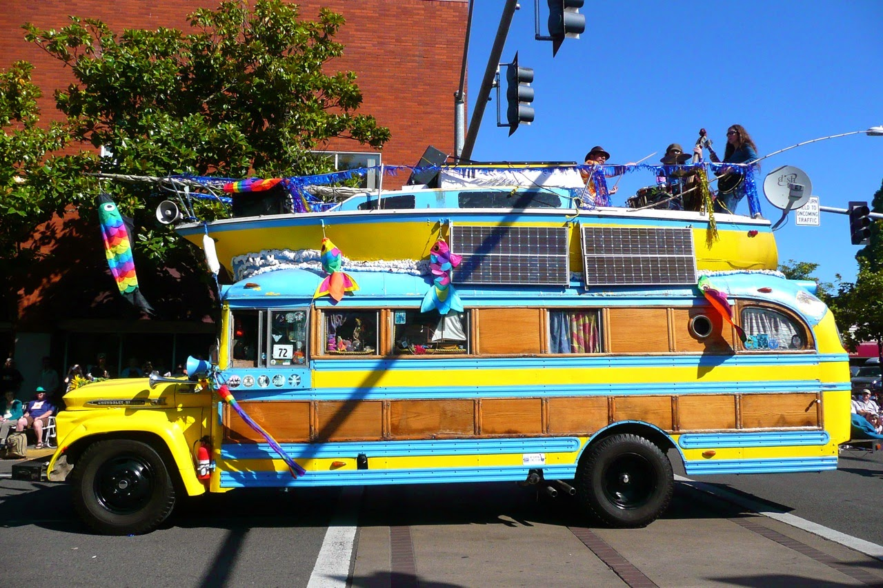 Eugene Celebration parade, hippie bus, band on boat, boat on top of bus, downtown traffic